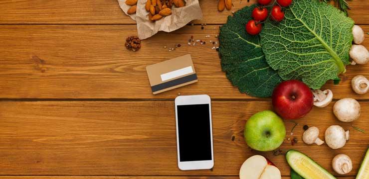 celular, cartão de crédito e legumes em cima de mesa de madeira